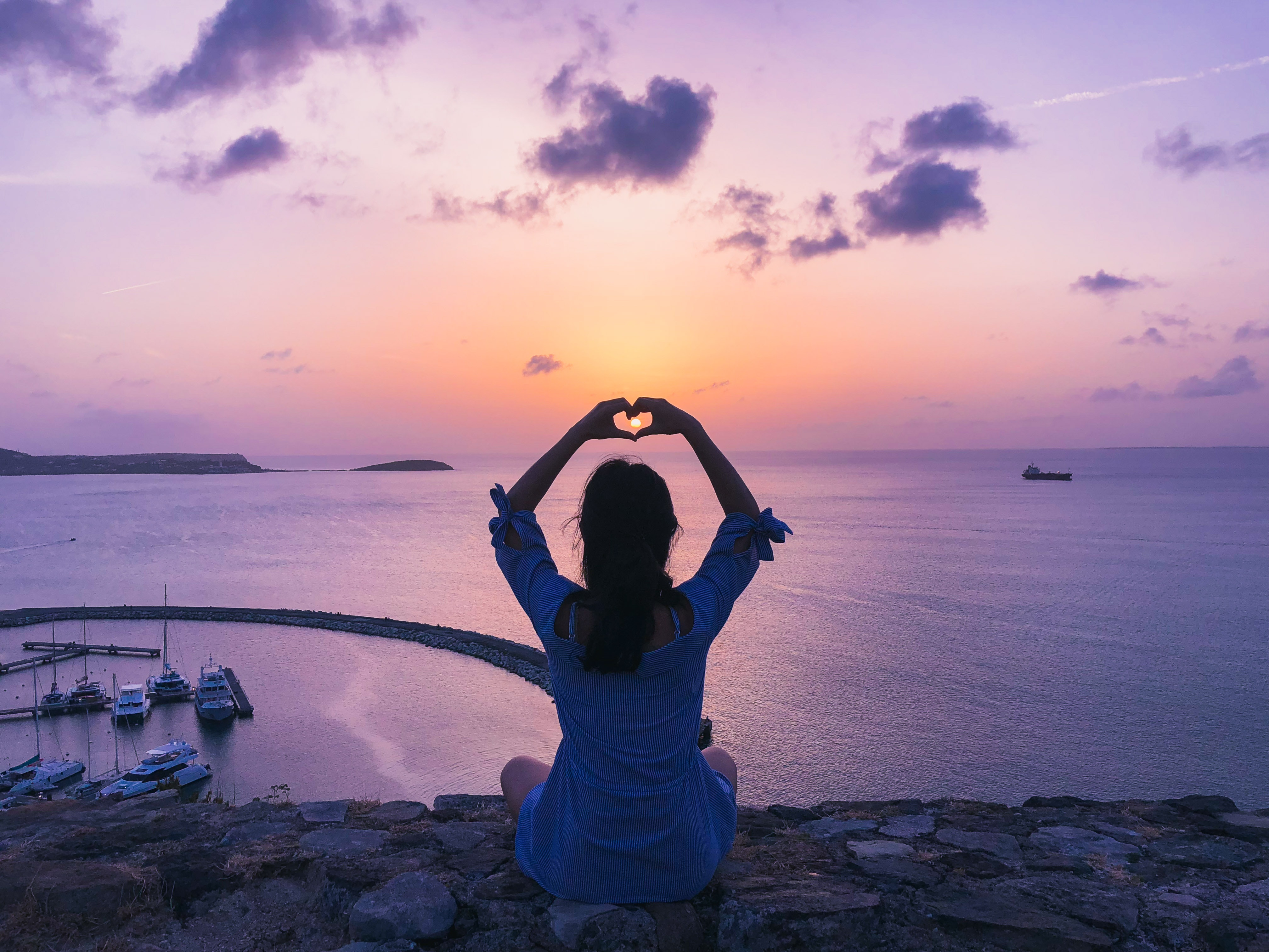 woman-sitting-on-rock-doing-heart-hand-gesture-1399034