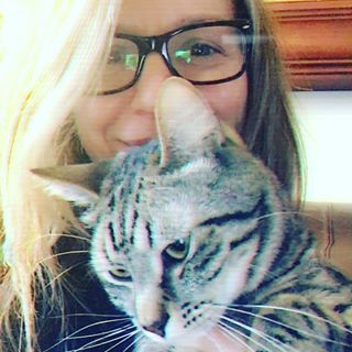 Photo of author Kristen Casey wearing glasses and holding a tabby cat.